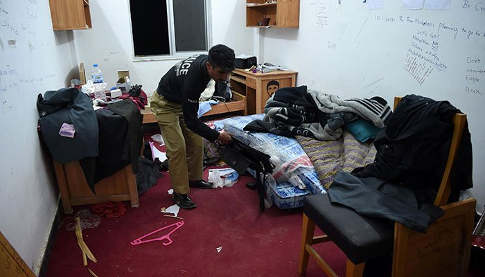A Pakistani policeman inspect a room of a student Mashal Khan, who was killed by classmates, at a hostel at Abdul Wali Khan university in Mardan
