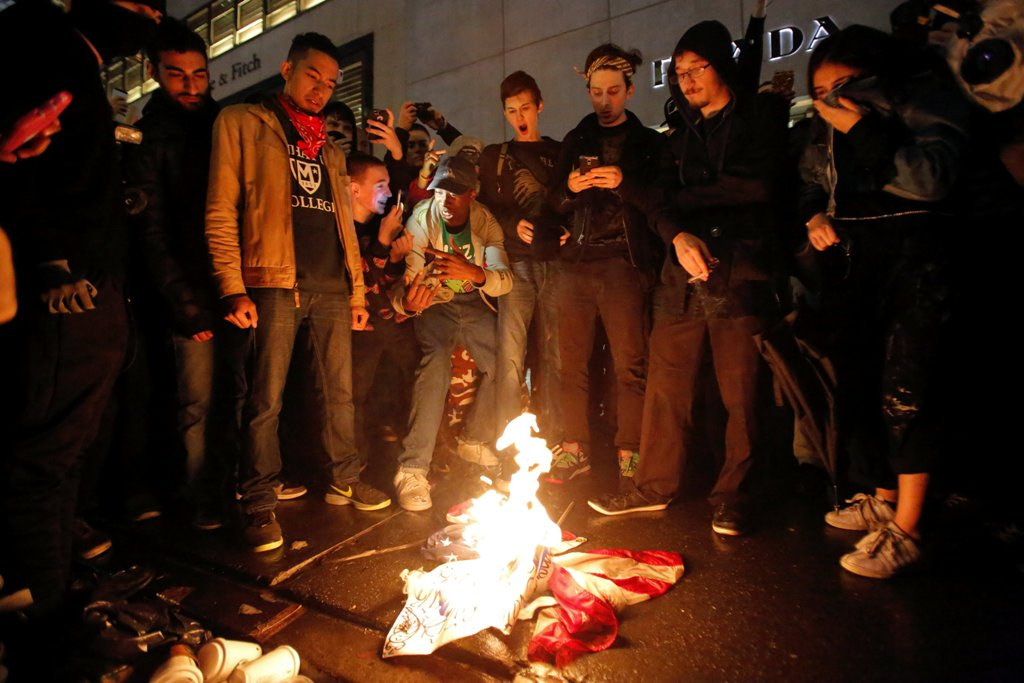 Demonstrators burn the U.S. flag outside Trump Tower during a march against President-elect Donald Trump in Manhattan, New York