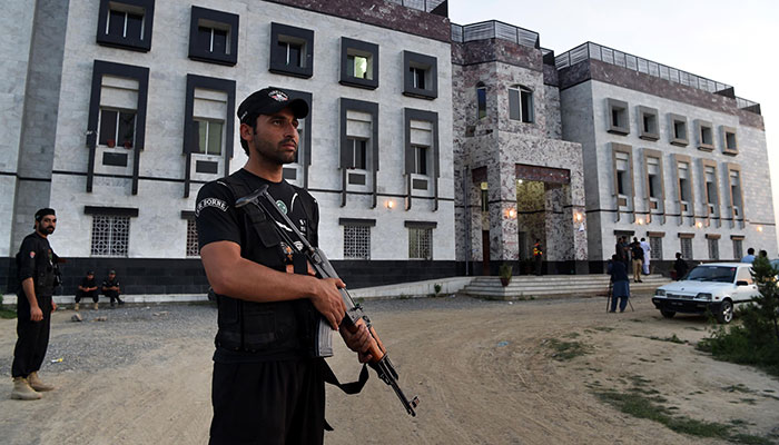 Pakistani policemen stand guard outside the hostel at Abdul Wali Khan university where students beat to death a classmate in Mardan — AFP