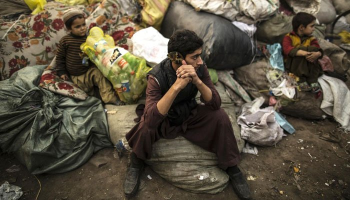 Afghan refugees sit on sacks filled with used plastic items to sell at their makeshift shelter in a slum on the outskirt of Lahore January 12, 2015.—Photo by Reuters