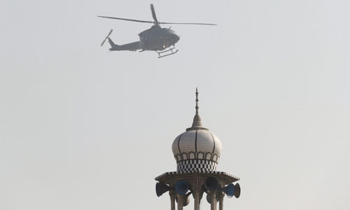 Photo shows military helicopter flying overhead during operation