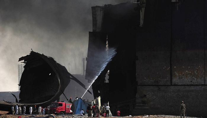 Labourers look on as the fire fighters attempt to put out the fire. PHOTO: AFP