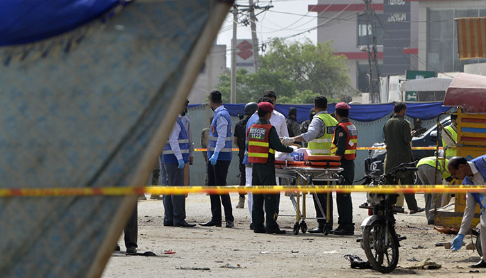 Pakistani security officials collect evidence from the scene of a suicide bomb attack on a census team in Lahore – AFP