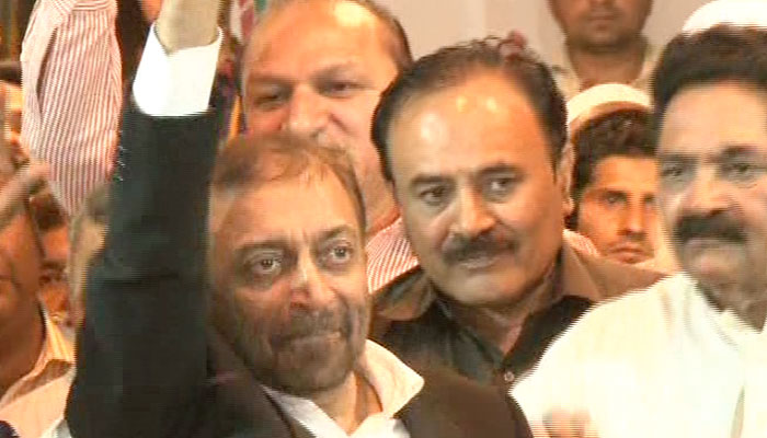 Sattar waves at his supporters after he was released from police detention
