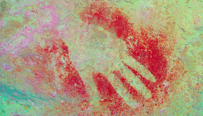 A prehistoric hand painting, seen on a wall of the Maltravieso cave in Caceres, Spain/AFP