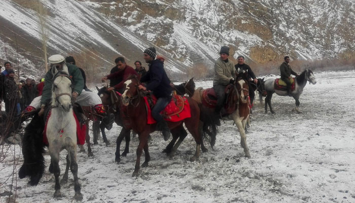 Pakistani horsemen compete for a cattle carcass during a game of the traditional sport of Buzkashi in snow covered Chapursan village of Hunza Valley/AFP