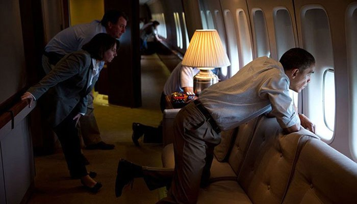 May 26, 2013. The President and members of the White House staff look out the window of Air Force One to view tornado damage over Moore, Oklahoma. After landing at Tinker Air Base, the President did a walking tour of the damage and met with those affected
