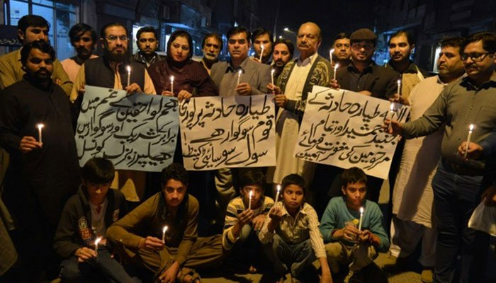 Pakistani people hold candles in memory of victims of plane crash in Multan on December 7, 2016- AFP