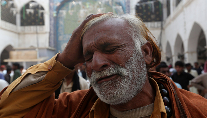 A man beats his head as he mourns the death of a relative who was killed in a suicide blast. February 17, 2017. REUTERS/Akhtar Soomro