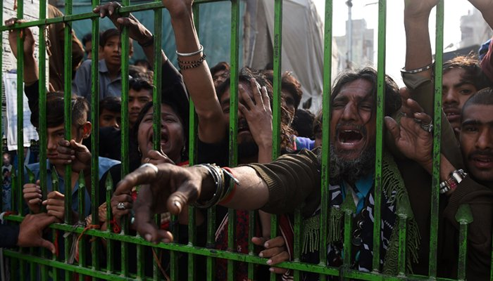 Pakistani devotees react as they gather outside the closed gate of the shrine of 13th century Muslim Sufi saint Lal Shahbaz Qalandar a day after AFP / ASIF HASSAN