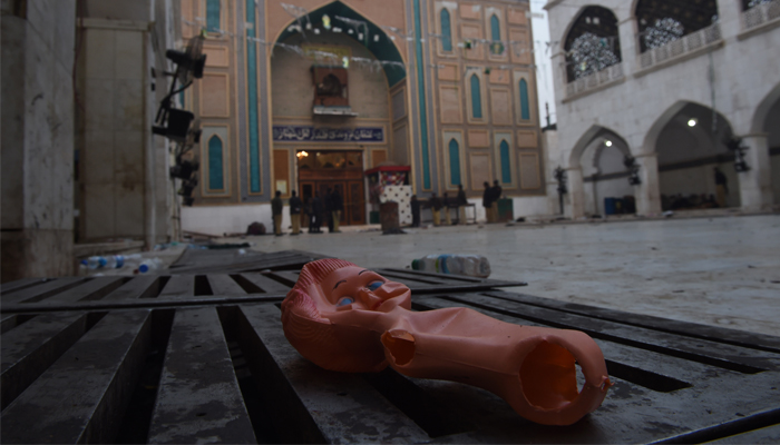 A doll lies on the ground at the 13th century shrine of Muslim Sufi Lal Shahbaz Qalandar a day after the bomb attack. AFP/ASIF HASSAN