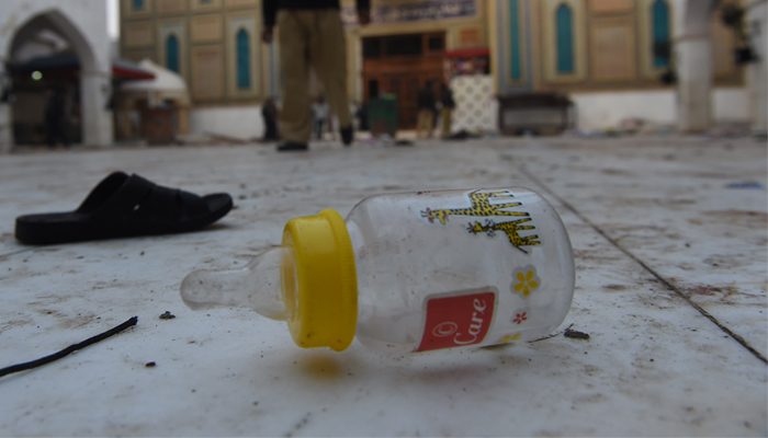 Slippers and a baby feeder of blast victims lie on the ground at the 13th century Muslim Sufi shrine. AFP / ASIF HASSAN