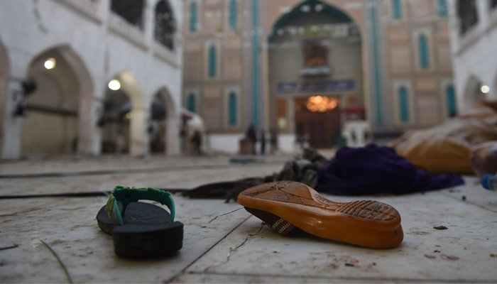 Slippers of blast victims lie on the ground at the 13th century Muslim Sufi shrine of Lal Shahbaz Qalandar. AFP / ASIF HASSAN