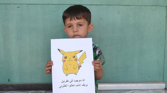 Syrian children hold Pokémon photos urging people to find and save them