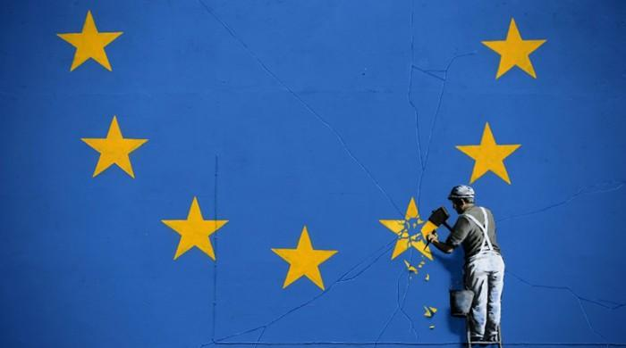 Banksy chips away at EU flag in first Brexit mural