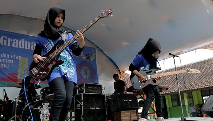 Widi Rahmawati (L) and Firdda Kurnia, members of the heavy metal band Voice of Baceprot, perform during a school's farewell event in Garut, Indonesia, May 15, 2017. REUTERS/Yuddy Cahya