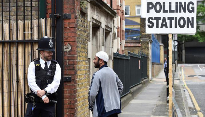 A police officer stands on duty outside a polling station in Tower Hamlets, London - Reuters