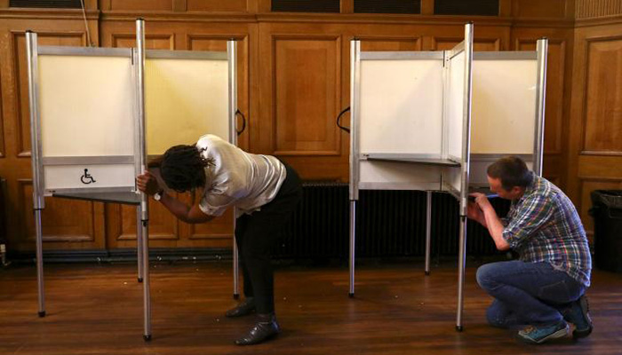 Workers assemble a polling booth inside a polling station on general election day in London - Reuters