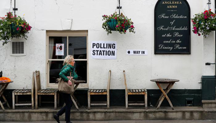 A woman walks past a public house in Kensington used as a temporary polling station, London, Britain June 8, 2017 - Reuters