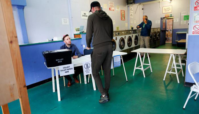 A man votes at a laundrette used as a temporary polling station in Oxford, Britain, June 8, 2017 - Reuters