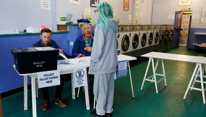 A woman votes at a laundrette used as a temporary polling station in Oxford , Britain, June 8, 2017 - Reuters