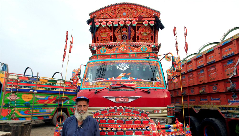 A security guard poses for a portrait in front of his favourite decorated truck at a truck stop outside Faisalabad, Pakistan, May 3, 2017. REUTERS/Caren Firouz