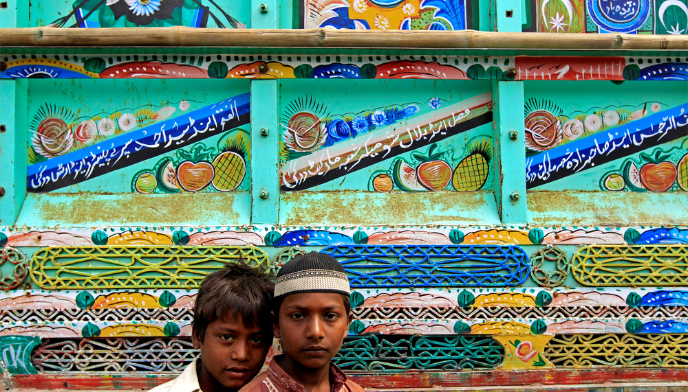 Boys pose for a picture in front of a decorated truck in Peshawar, Pakistan, May 2, 2017. REUTERS/Caren Firouz