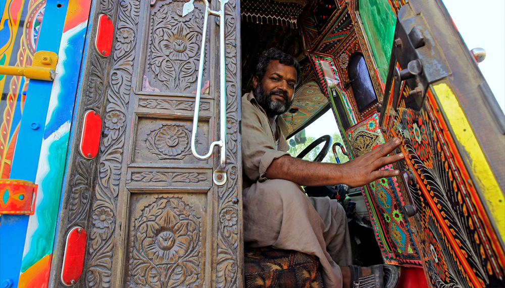 A driver holds open the door of the carved wood cab of his decorated truck in Faisalabad, Pakistan, May 4, 2017. REUTERS/Caren Firouz