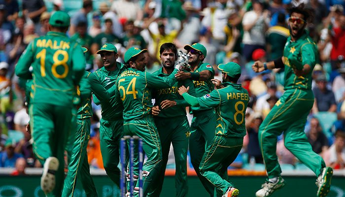 Pakistan's Mohammad Amir celebrates with teammates after taking the wicket of India's Virat Kohli.—Reuters photo