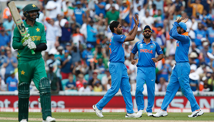 India´s Bhuvneshwar Kumar (2nd L) celebrates with teammates after taking the wicket of Pakistan´s Shoaib Malik (L) - AFP