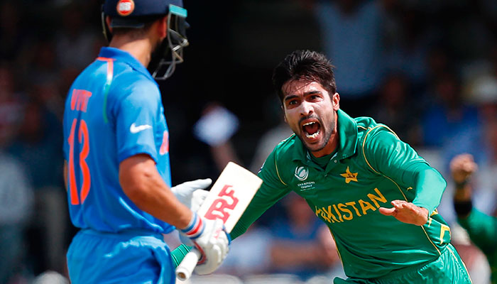 Amir celebrates after taking the wicket of India´s captain Virat Kohli (L) during the ICC Champions Trophy final cricket match between India and Pakistan at The Oval in London on June 18, 2017.—AFP photo