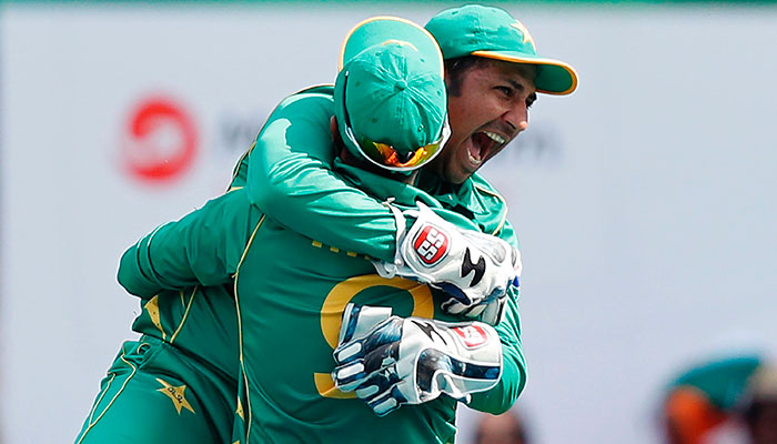 Pakistan´s Sarfraz Ahmed jumps into the arms of Pakistan´s Imad Wasim after he catches India´s MS Dhoni during the ICC Champions Trophy final cricket match between India and Pakistan at The Oval in London on June 18, 2017.—AFP photo