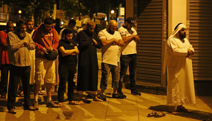 Men pray after a vehicle collided with pedestrians near a mosque in the Finsbury Park neighborhood of North London, Britain, June 19, 2017. REUTERS/Neil Hall
