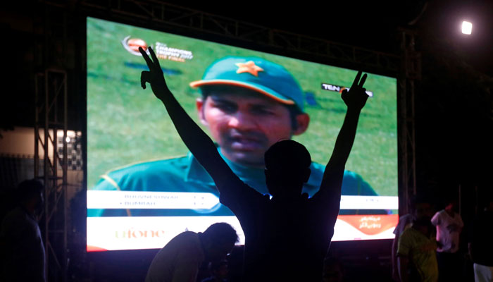 A Pakistani cricket fan makes a victory sign after Pakistan defeated India in the ICC Champions Trophy finals, in Karachi