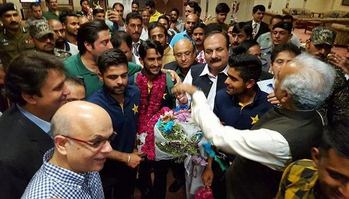 Player of the Tournament Hasan Ali surrounded by fans upon arrival in Lahore