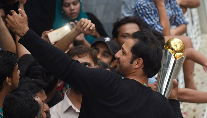 Victorious captain Sarfraz Ahmed clicks a selfie with the fans upon return to Karachi/AFP