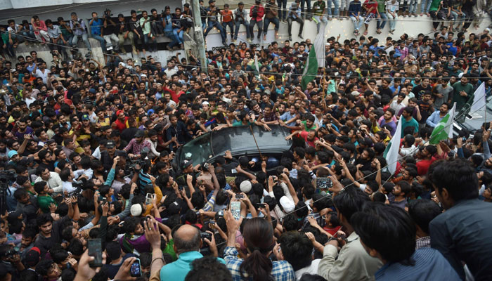 Fans surround Sarfraz Ahmed's car outside his home in Karachi/AFP