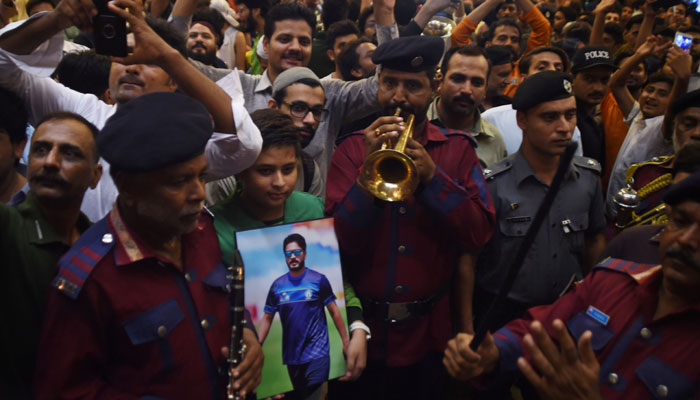 Fans gather outside Karachi airport to welcome Sarfraz Ahmed and Rumman Raees/AFP