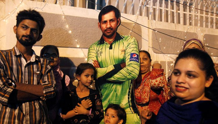 Fans carry Sarfraz Ahmed's poster to welcome him home/Reuters