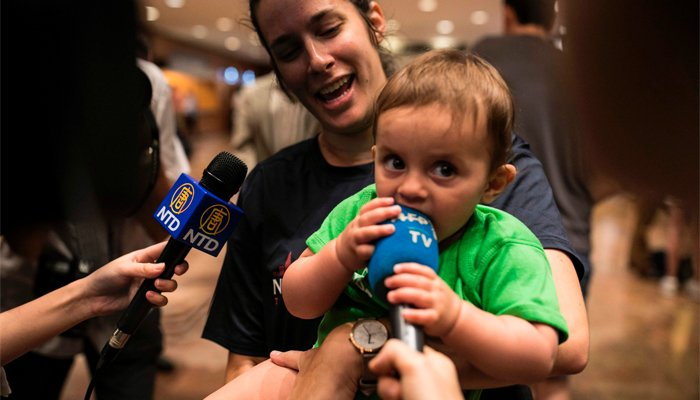 The first place finisher, 11-month-old Brooke Bender, chews on a television microphone as she is held by her mother Kristy after the NYC Triathlon's annual Diaper Derby, July 14, 2017, in New York City. AFP/Dominick Reuter