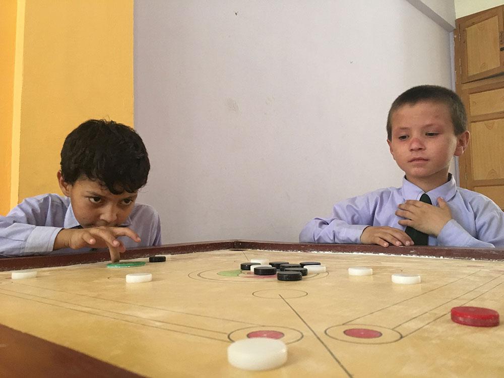 Students enjoying a game of carrom at Zamung Kor