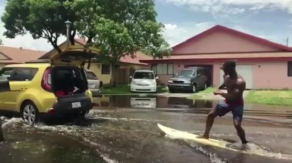 Florida men cruise flooded street on surfboard