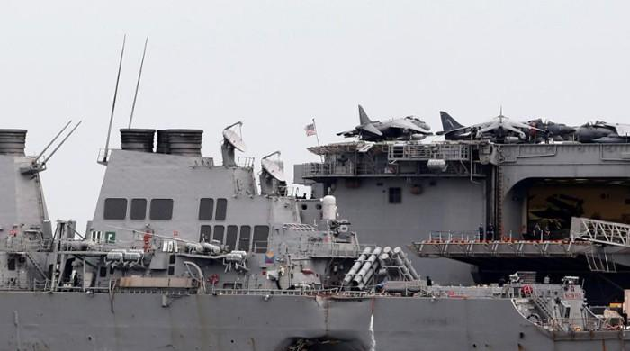 US divers find body remains in hull of damaged destroyer
