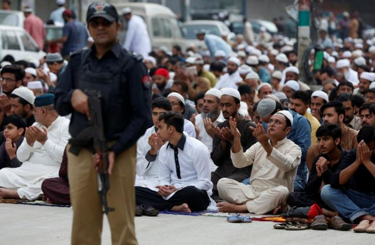 A policeman stands guard as people pray before a sacrifice slaughter during Eid-ul-Azha celebrations in Karachi, Pakistan, September 2, 2017/REUTERS