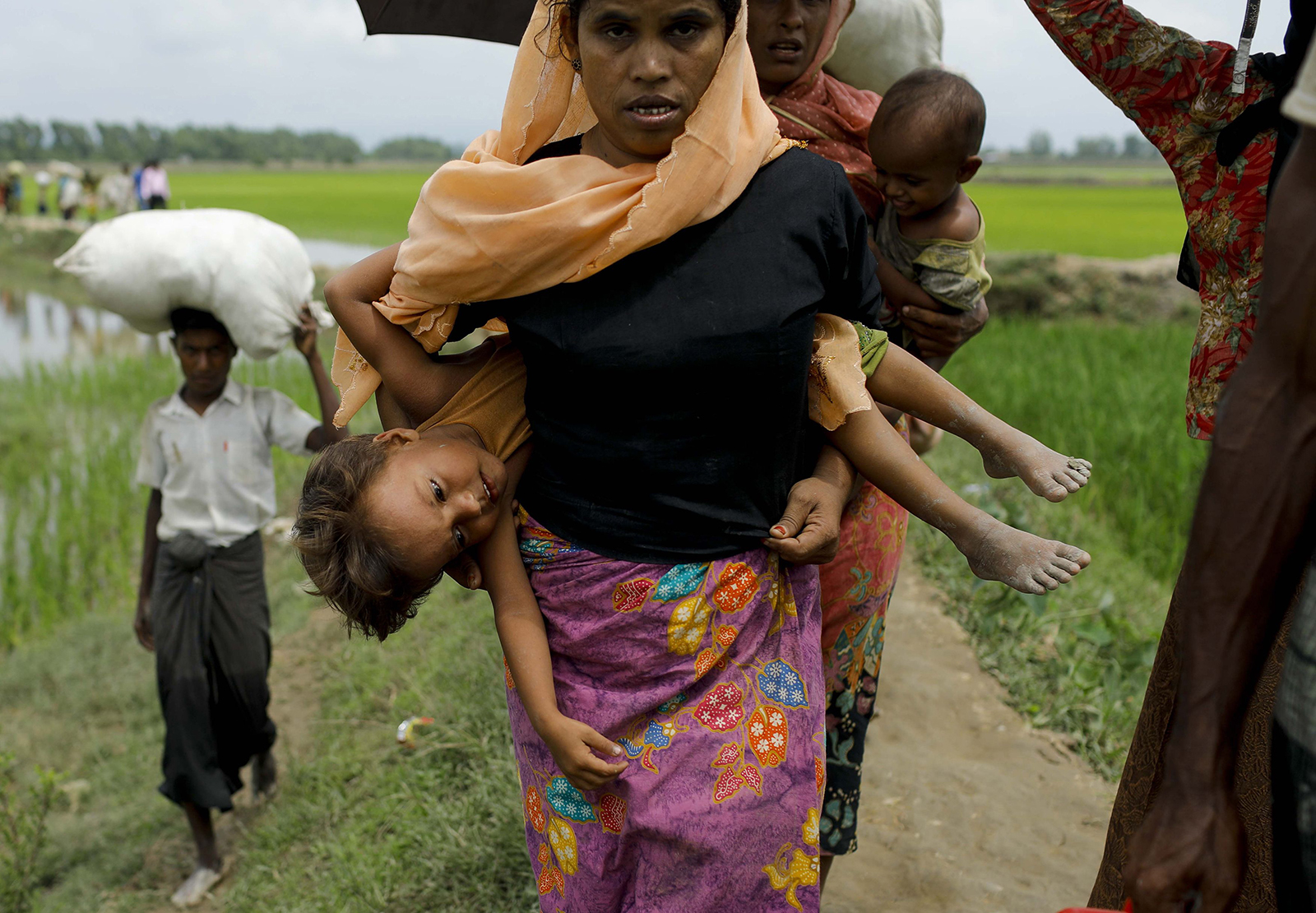 A Rohingya Muslim refugee carries a child as they arrive from Myanmar through Lomba Beel after crossing the Naf river, in the Bangladeshi town of Teknaf on September 7, 2017 - AFP