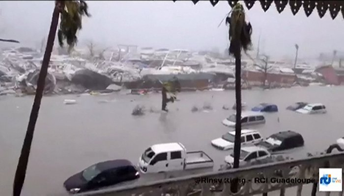 A handout grab image made from a video released on September 6, 2017 by RCI.fm shows flooded streets and damage on the French overseas island of Saint-Martin, filmed from a terrace of the Beach Plaza hotel - AFP