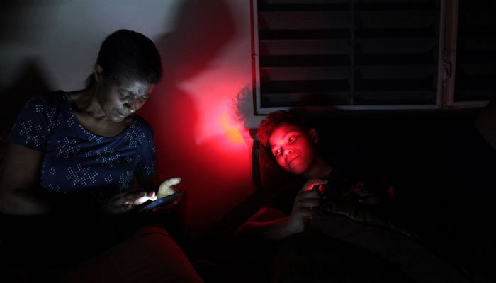 Angie Rodriguez (L) sits with her grandson at their home during a blackout after Hurricane Irma rolled by the US territory´s northern coast, in San Juan, Puerto Rico September 7, 2017/REUTERS