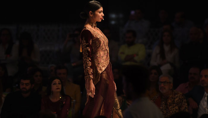 A model walks the ramp in a dress by designer Obaid Sheikh. Photo: AFP