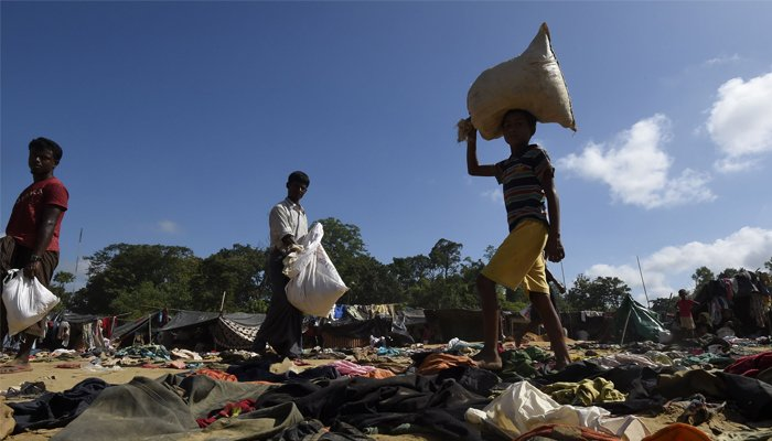 Rohingya Muslim refugees walk past discarded clothing on the ground at the Bhalukali refugee camp near Ukhia on September 16, 2017. AFP/Dominique Faget