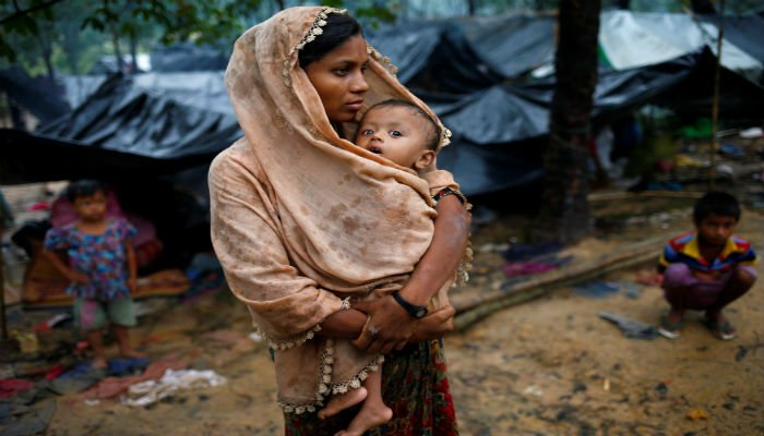 A Rohingya refugee woman wraps her child with a scarf as it drizzles in Cox´s Bazar, Bangladesh, September 17, 2017.  Photo: REUTERS
